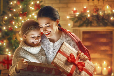 Foto de Merry Christmas and Happy Holiday! Loving family mother and child with magic gift box. - Imagen libre de derechos