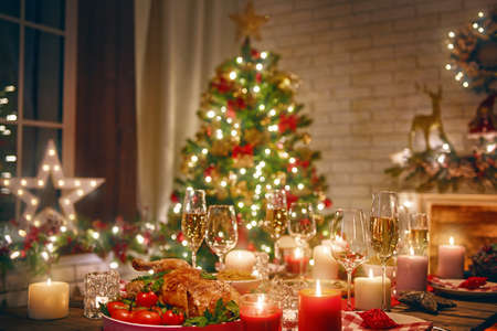 Foto per Merry Christmas and Happy New Year! A beautiful living room decorated for holidays. Table served to the dinner. - Immagine Royalty Free