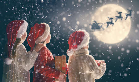 Foto de Merry Christmas and happy holidays! Cute little children with xmas presents. Santa Claus flying in his sleigh against moon sky. Kids enjoying the holiday with gifts on dark background. - Imagen libre de derechos