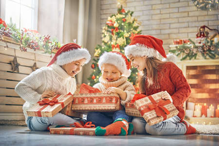Photo for Merry Christmas and Happy Holidays! Cheerful cute children opening gifts. Kids having fun near tree in the morning. Loving family with presents in room. - Royalty Free Image