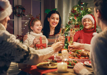 Foto per Merry Christmas! Happy family are having dinner at home. Celebration holiday and togetherness near tree. - Immagine Royalty Free