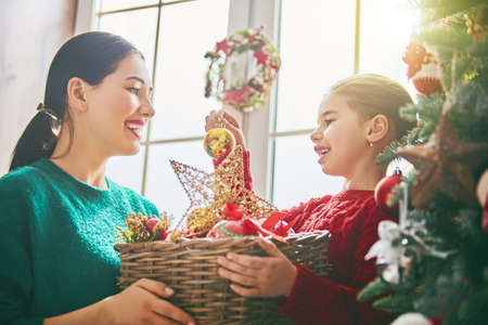 Foto de Merry Christmas and Happy Holidays! Mom and daughter decorate the tree indoors. The morning before Xmas. Portrait loving family close up. - Imagen libre de derechos