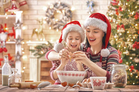 Foto de Merry Christmas and Happy Holidays. Family preparation holiday food. Mother and daughter cooking cookies. - Imagen libre de derechos