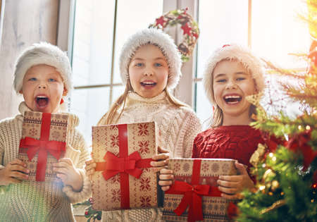 Photo pour Merry Christmas and Happy Holidays! Cheerful cute children opening gifts. Kids having fun near tree in the morning. Loving family with presents in room. - image libre de droit