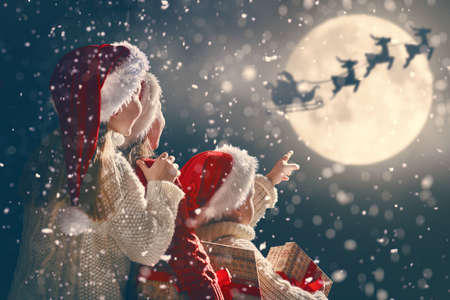 Photo for Merry Christmas and happy holidays! Cute little children with xmas presents. Santa Claus flying in his sleigh against moon sky. Kids enjoying the holiday with gifts on dark background. - Royalty Free Image