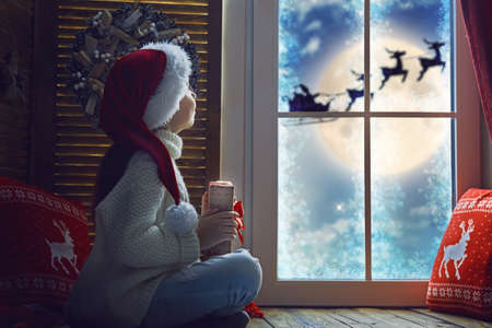 Photo for Cute little child girl sitting by window and looking at Santa Claus flying in his sleigh against moon sky. Room decorated on Christmas. Kid enjoy the holiday.  - Royalty Free Image