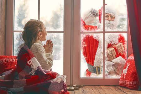 Photo for Cute little child girl is sitting by window and looking at Santa Claus knocking at home. Room decorated on Christmas. Kid enjoy the holiday.  - Royalty Free Image