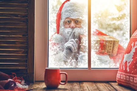 Foto de Merry Christmas! Santa Claus is knocking at window. Room decorated for holidays. View indoors home. - Imagen libre de derechos