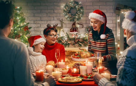 Photo for Merry Christmas! Happy family are having dinner at home. Celebration holiday and togetherness near tree. - Royalty Free Image