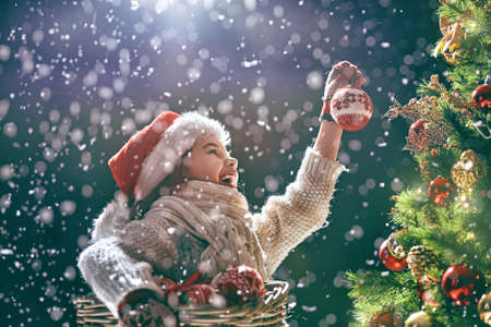 Photo pour Merry Christmas and Happy Holidays! Cute little child decorating the tree outdoors. Xmas night. - image libre de droit