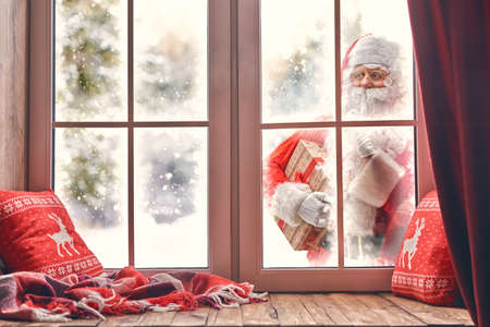 Photo for Merry Christmas! Santa Claus is knocking at window. Room decorated for holidays. View indoors home. - Royalty Free Image