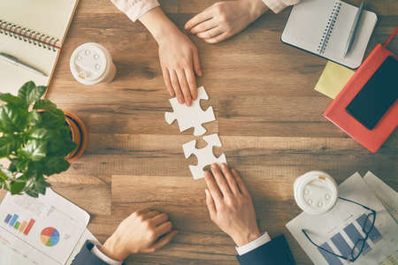 Foto de Man and woman working in the office. Collaborative teamwork. People are trying to connect couple puzzle piece. Symbol of association and connection. Concept of business strategy. - Imagen libre de derechos