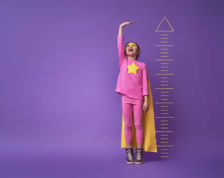 Foto de Little child is playing superhero. Kid is measuring the growth on the background of bright ultraviolet wall. Girl power concept. Yellow, pink and  purple colors. - Imagen libre de derechos