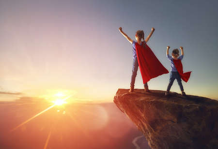 Foto de Two little children are playing superhero. Kids on the background of sunset sky. Girl power concept - Imagen libre de derechos