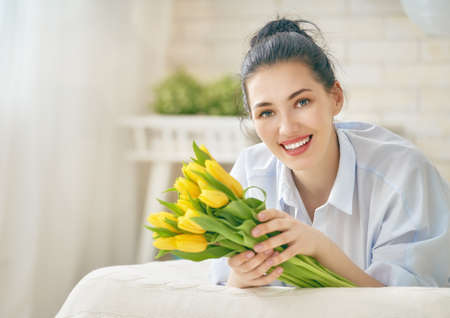 Foto de Beautiful young woman in the blue dress with flowers tulips in hands on bed at home. - Imagen libre de derechos