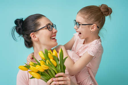 Photo for Happy women's day! Child daughter is congratulating mom and giving her yellow flowers tulips. Mum and girl smiling and hugging on light blue background. Family holiday and togetherness. - Royalty Free Image