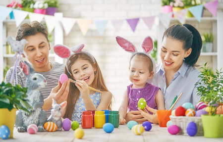 Photo pour Mother, father and daughters are painting eggs. Happy family are preparing for Easter. Cute little children girls wearing bunny ears. - image libre de droit