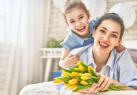 Photo for Happy women's day! Child daughter is congratulating mom and giving her flowers tulips. Mum and girl smiling and hugging. Family holiday and togetherness. - Royalty Free Image