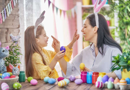 Foto de Happy holiday! A mother and her daughter are painting eggs. Family preparing for Easter. Cute little child girl is wearing bunny ears. - Imagen libre de derechos