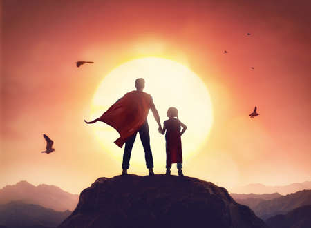 Foto de Happy loving family. Father and his daughter playing outdoors. Daddy and his child girl in an Superhero's costumes. - Imagen libre de derechos
