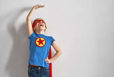 Foto de Little child is playing superhero. Kid is measuring the growth on the background of wall. Girl power concept.  - Imagen libre de derechos