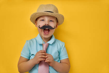 Foto de Funny time. Happy father's day! Boy playing and holding paper mustache on stick and pretending of daddy. - Imagen libre de derechos
