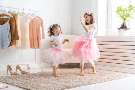 Foto de Happy girls dressing up at home. Funny lovely children are having fun in room. - Imagen libre de derechos