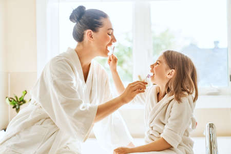 Foto de Happy family! Mother and daughter child girl are brushing teeth toothbrushes in the bathroom. - Imagen libre de derechos