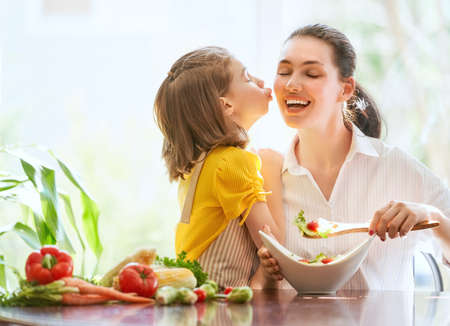 Foto de Healthy food at home. Happy family in the kitchen. Mother and child daughter are preparing the vegetables. - Imagen libre de derechos