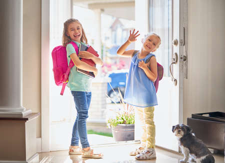 Photo for Pupils of primary school. Girls with backpack is going to school from home. Beginning of lessons. First day of fall. - Royalty Free Image