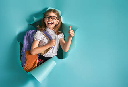 Photo pour Back to school and happy time! Cute industrious child is breaking through color paper wall. Kid with backpack. Girl ready to study. - image libre de droit