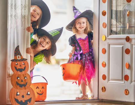 Photo for Happy Halloween! Three cute little laughing girls in witches costumes are coming to the house for sweets. - Royalty Free Image
