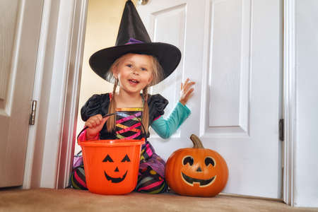 Photo for Happy Halloween! Cute little laughing girl in witch costume with a pumpkin. - Royalty Free Image