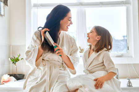 Photo pour Happy family! Mother and daughter child girl are combing hair in the bathroom. - image libre de droit