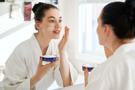 Foto de Beautiful young woman with cream for her face looking in the mirror in bathroom at home. Facial treatment. Cosmetology, beauty and spa. - Imagen libre de derechos
