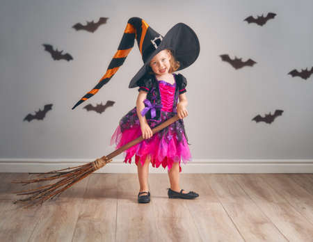 Photo for Happy Halloween! Cute little laughing girl in witch costume with a broomstick. - Royalty Free Image