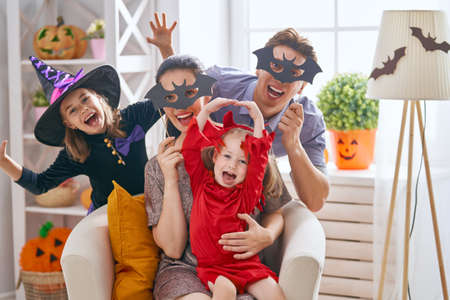 Foto de Mother, father and their kids having fun at home. Happy family celebrating Halloween. Children wearing carnival costumes. - Imagen libre de derechos