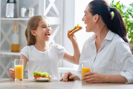 Foto de Healthy food at home. Happy family in the kitchen. Mother and child daughter are having breakfast. - Imagen libre de derechos
