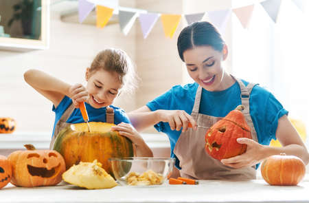 Photo for Happy Halloween! Mother and her daughter carving pumpkin. Family preparing for holiday. - Royalty Free Image