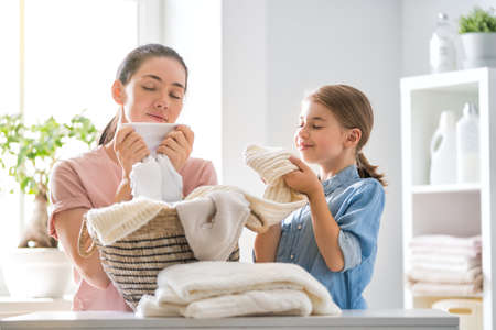Photo for Beautiful young woman and child girl little helper are having fun and smiling while doing laundry at home. - Royalty Free Image
