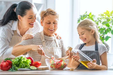 Foto de Healthy food at home. Happy family in the kitchen. Grandma, mother and child daughter are preparing the vegetables and fruit. - Imagen libre de derechos