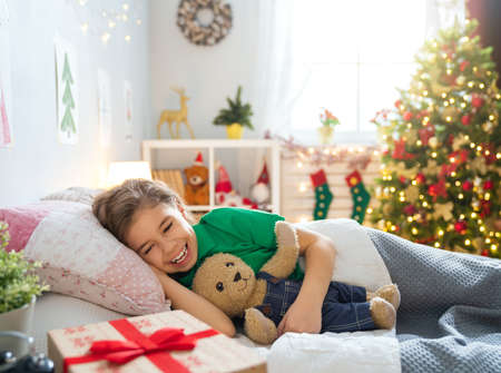 Photo pour Merry Christmas and Happy Holiday! Cute little child girl sleeping in the bed near tree at home. - image libre de droit