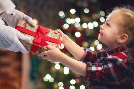 Photo pour Merry Christmas and Happy Holidays! Hands of Santa Claus giving a x-mas gift to child. - image libre de droit