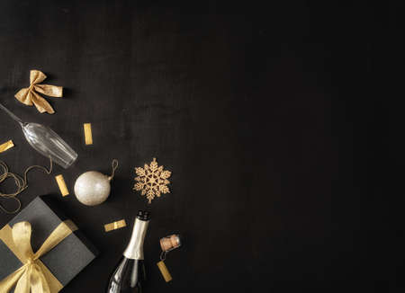 Foto de Happy New Year! Baubles, gift boxes and bottle of sparkling wine on black desk. Top view. Holiday traditions. Space for your text. - Imagen libre de derechos