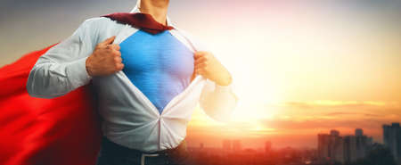 Foto de superhero businessman looking at city skyline at sunset. the concept of success, leadership and victory in business. - Imagen libre de derechos