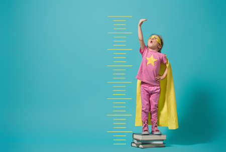 Photo pour Little child playing superhero. Kid measures the growth on the background of bright blue wall. Girl power concept. Yellow, pink and  turquoise colors. - image libre de droit