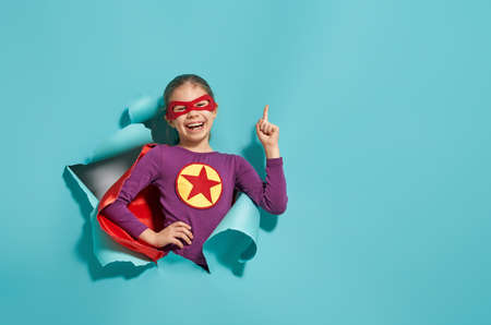 Foto de Little child is playing superhero. Kid on the background of bright blue wall. Girl power concept. - Imagen libre de derechos