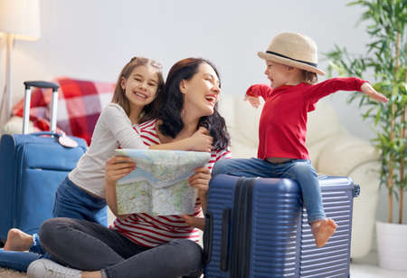 Foto per Go on an adventure! Happy family preparing for the journey. Mom and daughters are packing suitcases for the trip. - Immagine Royalty Free