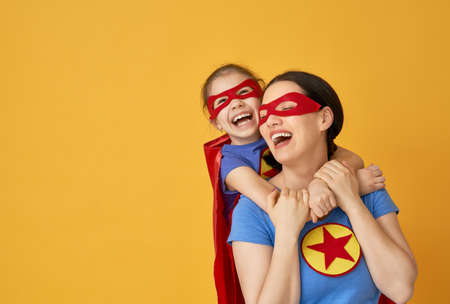 Foto de Mother and her child playing together. Girl and mom in Superhero costumes. Mum and kid having fun and smiling. Family holiday and togetherness. - Imagen libre de derechos