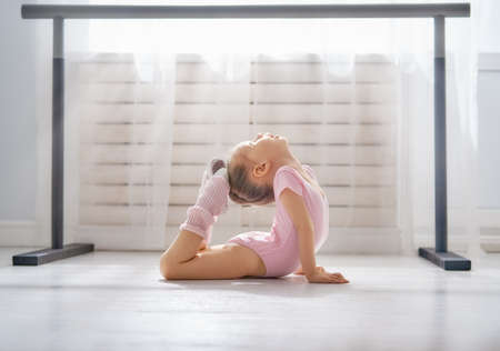 Photo pour Cute little girl dreams of becoming a ballerina. Child girl in a pink tutu dancing in a room. Baby girl is studying ballet. - image libre de droit